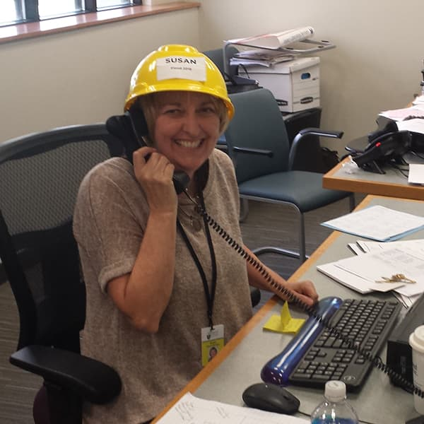 A photo of someone on the phone at The Portland Clinic wearing a yellow hard hat.