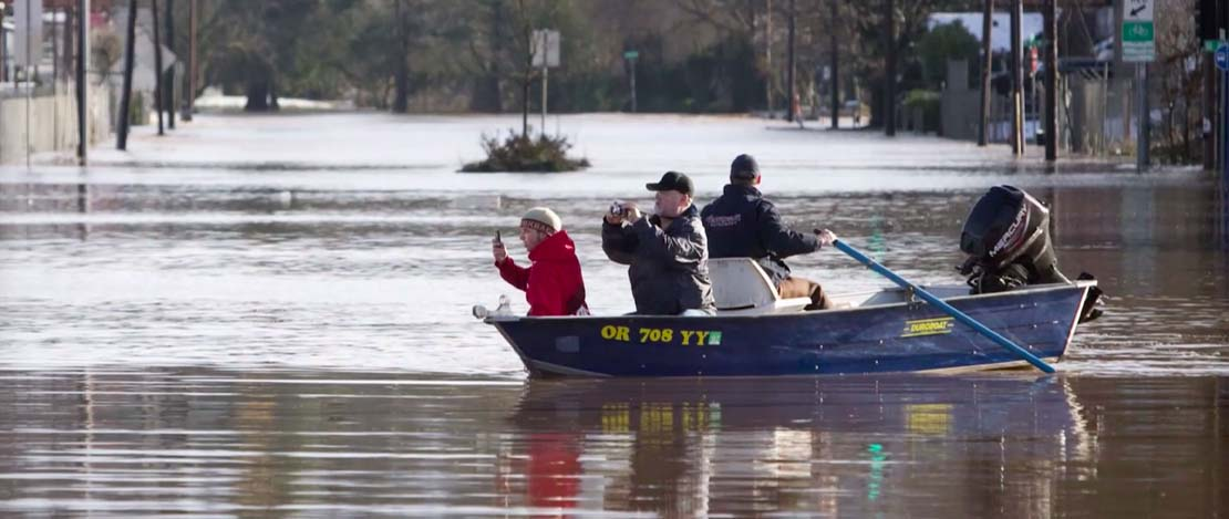 People taking photos from a small motorboat in the middle of a flooded street in Portland, Oregon.