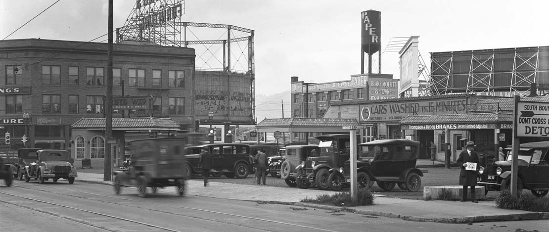 A black and white photo of a busy street in historic Portland, Oregon.