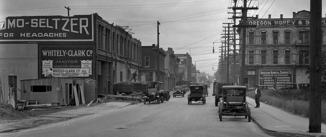 A black and white photo of cars driving on a busy street in historic Portland.