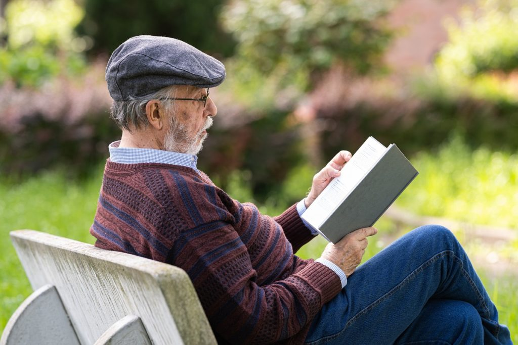 Senior man reading a book outside on a bench